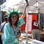 SCBWI Metro NY member Mackenzie Reide poses in a Statue of Liberty costume at the SCBWI booth at the Brooklyn Book Fair in September 2017